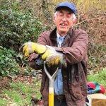 Man leaning on garden fork